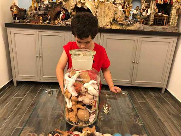 bambino guarda barattolo ocn pezzi di pastori del presepe Napoletano