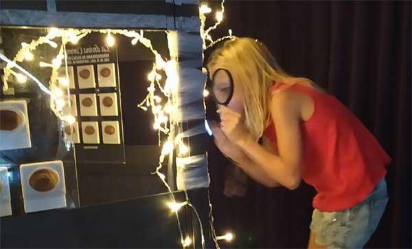 bambina in museo con lente di ingrandimento